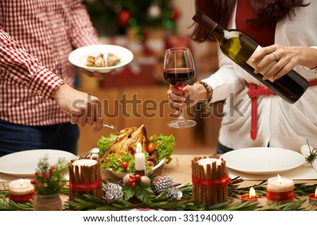 People eating roasted chicken and drinking red wine at Christmas dinner - stock photo