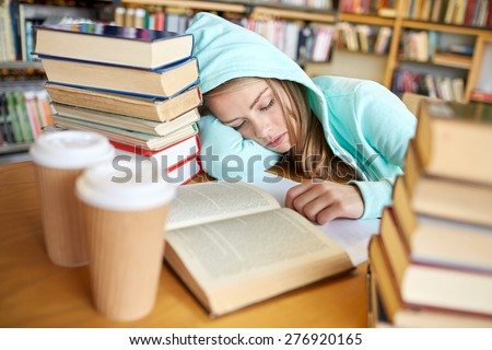 people, education, session, exams and school concept - tired student girl or young woman with books and coffee sleeping in library - stock photo
