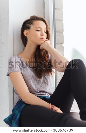 people, emotion and teens concept - sad unhappy pretty teenage girl sitting on windowsill - stock photo