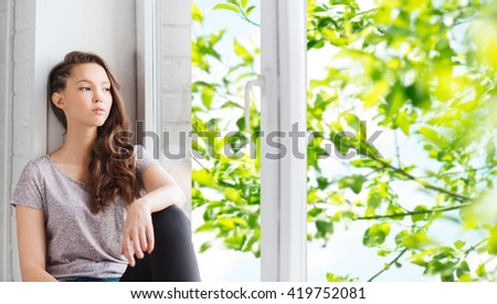 people, emotion and teens concept - sad unhappy pretty teenage girl sitting on windowsill and looking through window over green natural background - stock photo