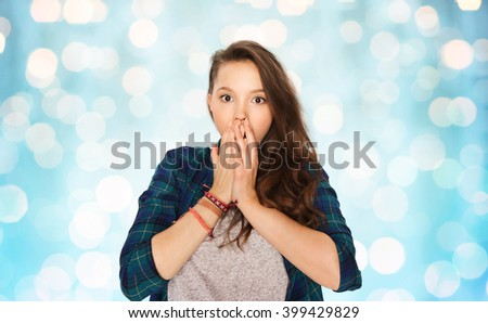 people, emotion, expression and teens concept - scared teenage girl over blue holidays lights background - stock photo