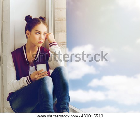people, emotion, technology and teens concept - sad unhappy pretty teenage girl sitting on windowsill with smartphone and looking to window
