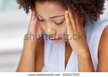 people, emotions, stress and health care concept - unhappy african american young woman touching her head and suffering from headache - stock photo