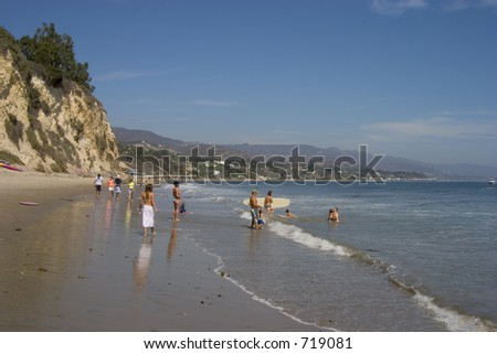 People enjoy a sunny day at the beach in southern California's Malibu. - stock photo