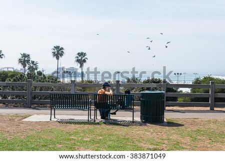 People enjoy the sea view from park bench