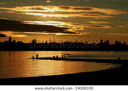 People enjoy the setting winter sun to fish on a sandbank on the Swan River in Perth Western Australia