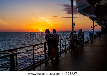 People enjoy the sunset onboard a cruise ship in the North Atlantic.