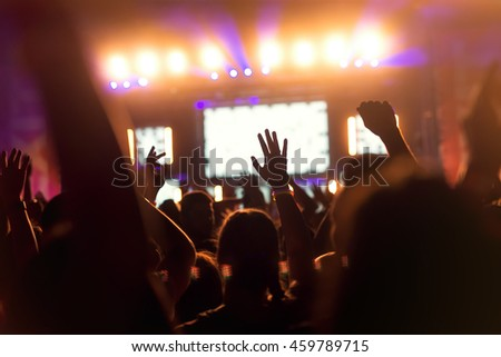 People enjoying a concert and holding their hands up.