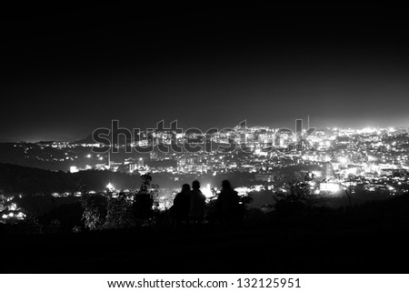 People enjoying distant city lights - stock photo