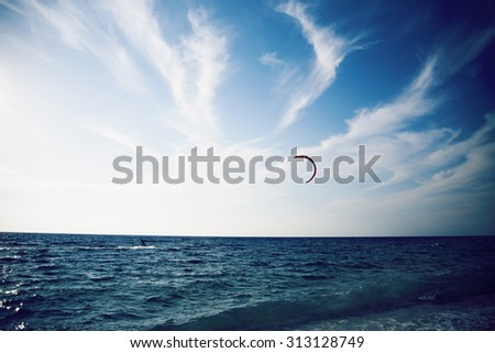 People enjoying kitesurfing on clear blue tropical water - stock photo