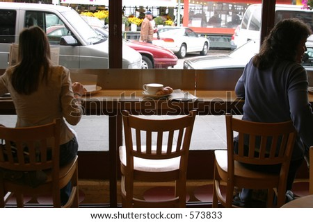 People enjoying Seattles favorite drink Coffee with the morning paper and morning traffic off to work and parts unknown