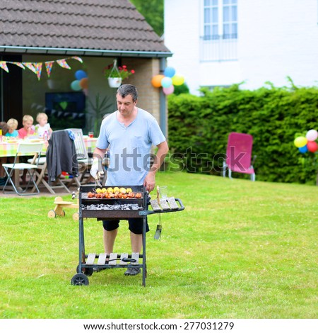 People enjoying summertime. A man cooking meat on barbecue for summer family dinner at the backyard of the house. - stock photo