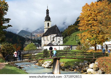 People enjoying the beautiful scenery on a bridge in front of a church with foggy mountains in the background ~ Splendid autumn scenery of Bavarian countryside in Ramsau Germany Europe - stock photo