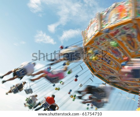 People enjoying the ride in a classic Chair-O-Planes at the fair - stock photo