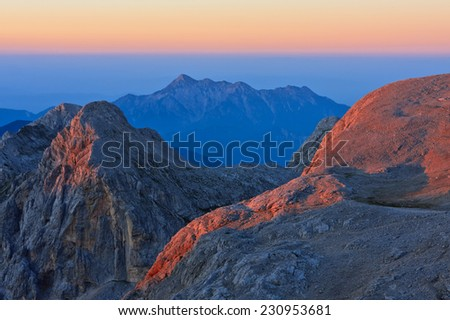 People enjoying the view of the sunset on a perfect summer day of the high mountain refugee Kredarica under the Triglav mountain the highest peak in the Julian Alps in Slovenia - stock photo