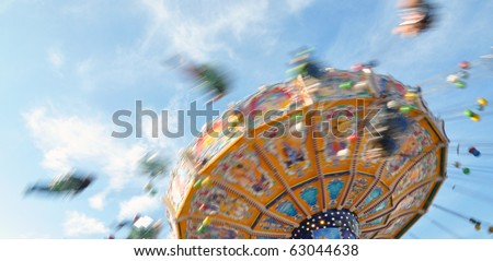 People enjoying their ride in a  classic Chair-O-Planes at the fair - stock photo