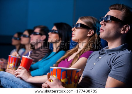 People enjoying three-dimensional movie. Young people in three-dimensional glasses watching movie while sitting at the cinema  - stock photo