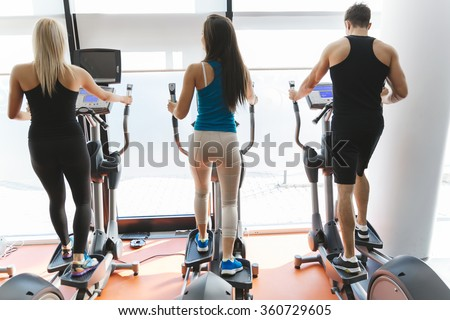 People exercising in gym to keep body in shape - stock photo