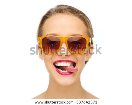 people, expression, joy and fashion concept - smiling young woman in sunglasses with pink lipstick on lips showing tongue - stock photo