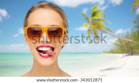 people, expression, summer vacation, travel and fashion concept - smiling young woman in sunglasses with pink lipstick on lips showing tongue over tropical beach with palm background - stock photo