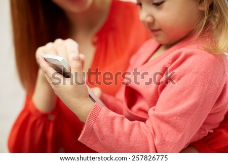 people, family and technology concept - close up of woman and little girl with smartphone - stock photo