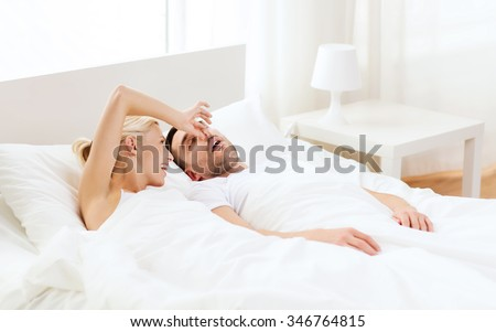 people, family, bedtime and couple concept - happy woman closing nose to her snoring man sleeping in bed at home - stock photo