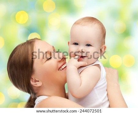 people, family, motherhood and children concept - happy mother hugging adorable baby with finger in his mouth over green lights background - stock photo