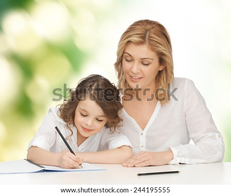 people, family, school, home education and parenting concept -happy mother and daughter doing homework and writing in notebook over green background - stock photo