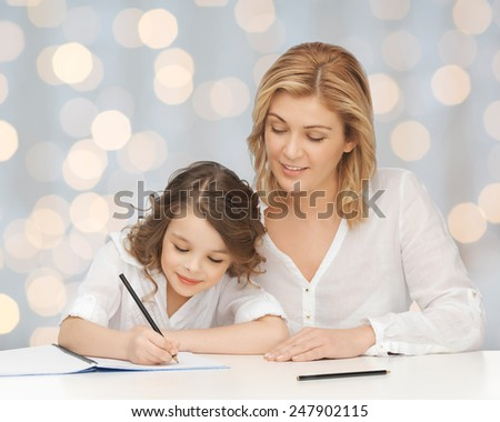 people, family, school, home education and parenting concept -happy mother and daughter doing homework and writing in notebook over holidays lights background - stock photo