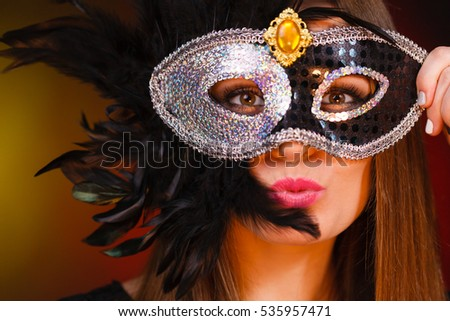 People, fashion, party concept. Sensual woman with carnival mask. Attractive young lady with long brown hair preaparing for celebration.