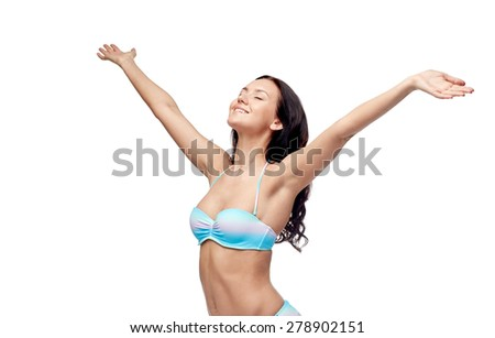 people, fashion, summer and beach concept - happy young woman in bikini swimsuit with raised hands looking up - stock photo