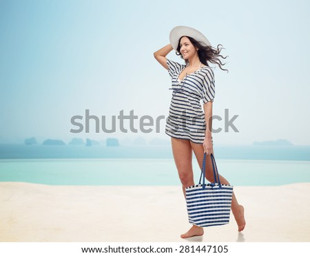 people, fashion, summer and beach concept - happy young woman in summer clothes and sun hat with bag over infinity pool at beach resort - stock photo