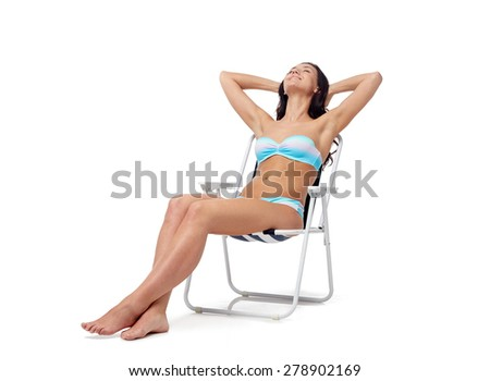people, fashion, swimwear, summer and beach concept - happy young woman in bikini swimsuit sunbathing on folding chair - stock photo