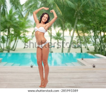 people, fashion, swimwear, summer and beach concept - happy young woman posing in white bikini swimsuit with raised hands over swimming pool at beach resort - stock photo