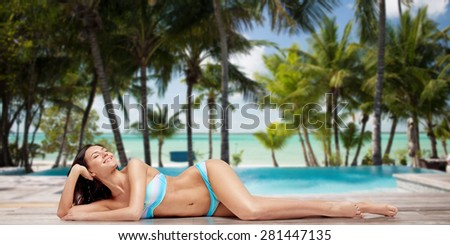 people, fashion, swimwear, summer and travel concept - happy young woman lying and tanning in bikini swimsuit over tropical beach with swimming pool background