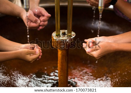 People filling up their hands with healthy mineral water from a wellspring in a spa (shallow DOF) - stock photo