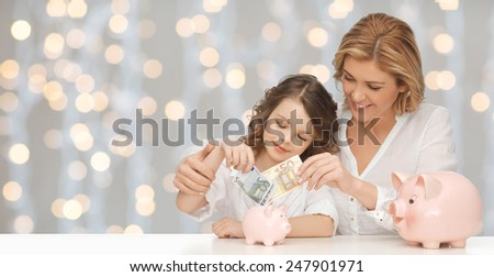 people, finances, family budget and savings concept - happy mother and daughter with piggy banks and paper money over lights background - stock photo