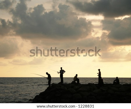 People fishing at sunset - stock photo
