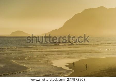 People fishing during sunset.  - stock photo