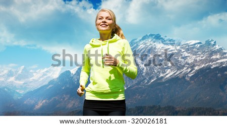 people, fitness, sport and healthy lifestyle concept - happy sporty woman running or jogging over nature - stock photo