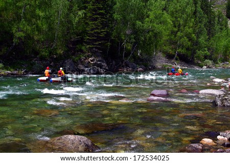 People float on a kayak on the mountain river - stock photo