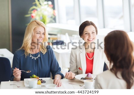 people, food, communication and lifestyle concept - happy women eating dessert and talking at restaurant - stock photo