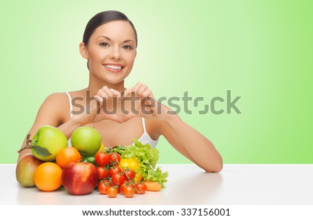 people, food, diet, healthy eating and weight loss concept - happy beautiful woman with fruits and vegetables showing heart shape hand sign over green background - stock photo