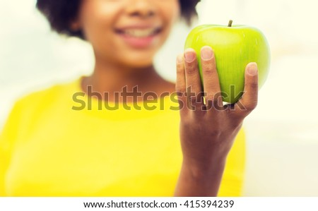 people, food, healthy eating and dental care concept - close up of happy african american young woman with green apple at home - stock photo