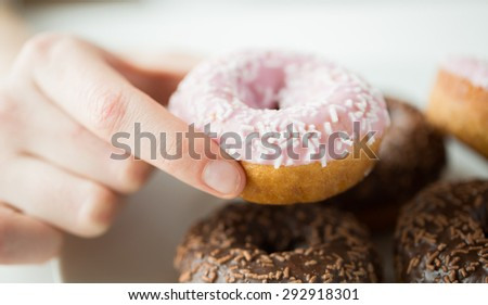 people, food, junk-food and eating concept - close up of female hand holding glazed donut - stock photo