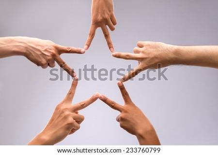 People forming star shape with their fingers - stock photo