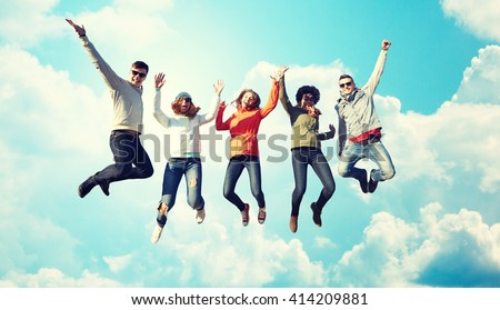 people, freedom, happiness and teenage concept - group of happy friends in sunglasses jumping high over blue sky and clouds background - stock photo