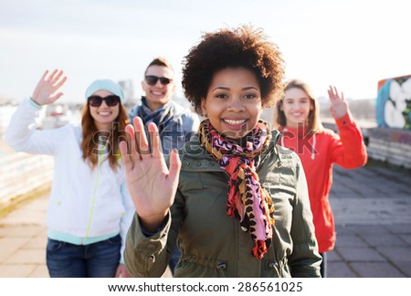 people, friendship and international concept - happy african american young woman or teenage girl in front of her friends waving hands on city street - stock photo