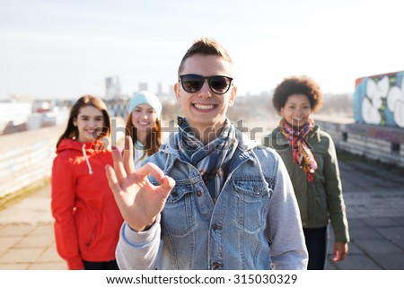 people, friendship and international concept - happy young man or teenage boy in front of his friends showing ok sign on city street - stock photo