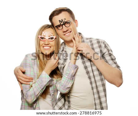 people, friendship, love and leisure concept - lovely couple holding party glasses on stick - stock photo